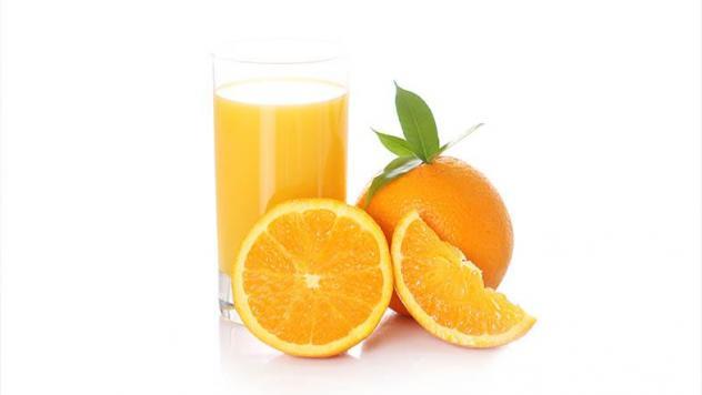 كوب من البرتقال و حبات من البرتقال